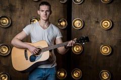 吉他弹奏者,音乐 一个年轻人弹在背景的一把声学吉他与在他后的光 水平的框架 免版税库存图片