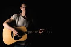 吉他弹奏者,音乐 一个年轻人弹在黑色被隔绝的背景的一把声学吉他 水平的框架 库存图片