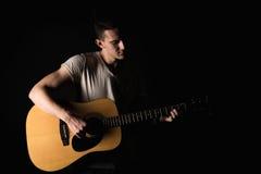 吉他弹奏者,音乐 一个年轻人弹在黑色被隔绝的背景的一把声学吉他 水平的框架 库存照片