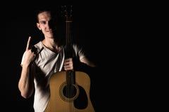 吉他弹奏者,音乐 一个年轻人站立与一把声学吉他并且显示他的手指,在黑色被隔绝的背景 水平的fra 库存照片