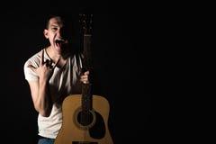 吉他弹奏者,音乐 一个年轻人站立与一把声学吉他并且显示他的舌头和手指在黑色被隔绝的背景 Hori 免版税库存照片