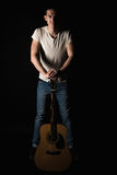 吉他弹奏者,音乐 一个年轻人站立与一把声学吉他,在黑色被隔绝的背景 垂直的框架 库存照片