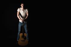 吉他弹奏者,音乐 一个年轻人站立与一把声学吉他,在黑色被隔绝的背景 水平的框架 库存照片