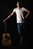 吉他弹奏者,音乐 一个年轻人站立与在黑色被隔绝的背景的一把声学吉他 垂直的框架 库存照片