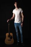 吉他弹奏者,音乐 一个年轻人站立与在黑色被隔绝的背景的一把声学吉他 垂直的框架 免版税图库摄影