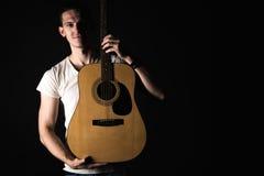 吉他弹奏者,音乐 一个年轻人站立与在黑色被隔绝的背景的一把声学吉他 水平的框架 图库摄影