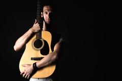 吉他弹奏者,音乐 一个年轻人站立与在黑色被隔绝的背景的一把声学吉他 水平的框架 库存图片