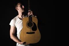 吉他弹奏者,音乐 一个年轻人站立与在黑色被隔绝的背景的一把声学吉他 水平的框架 免版税库存照片