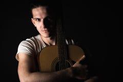 吉他弹奏者,音乐 一个年轻人站立与在黑色被隔绝的背景的一把声学吉他 水平的框架 免版税库存图片