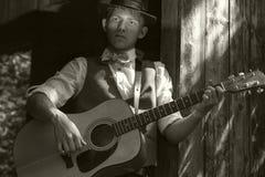 年轻吉他弹奏者画象。老影片减速火箭的作用 库存照片