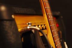 吉他的组合放大器有在黑背景的经典电吉他的 浅景深,低调,接近  免版税库存图片