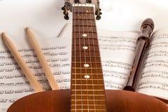 吉他脖子、鼓槌、记录器仪器和音乐板料 免版税库存照片