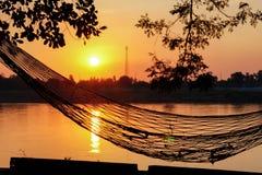 吊床日落河沿 图库摄影