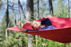吊床的女孩,森林 免版税库存照片