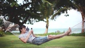吊床的年轻人使用在美丽的热带海滩的智能手机 1920x1080 股票视频