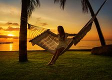吊床麻烦棕榈树的女孩享受一个热带假期的 免版税库存照片