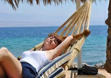 吊床laiyng的女孩在海 免版税库存图片