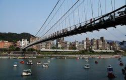 吊桥十字架河和小船 免版税库存照片