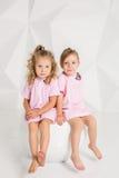 同一桃红色的两个小女朋友在有白色墙壁的一个演播室穿戴坐一把椅子 免版税图库摄影