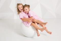同一桃红色的两个小女朋友在有白色墙壁的一个演播室穿戴坐一把椅子 免版税库存照片