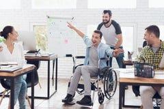 同事在办公室附近滚动轮椅的一个人 他们获得乐趣并且笑 免版税库存照片