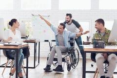 同事在办公室附近滚动轮椅的一个人 他们获得乐趣并且笑 库存照片