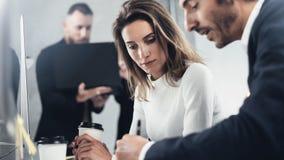 同事在工作过程中寻找企业解答在晴朗的办公室 遇见概念的商人 免版税库存图片