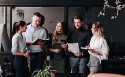 同事年轻队与文件一起使用和在一个时髦的现代办公室谈论项目 在的工作过程 库存照片