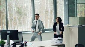 同事快乐的夫妇在有放松在工作以后的办公室乐趣移动的胳膊和身体一起跳舞 股票录像