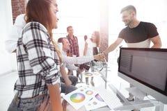 同事握手在一个创造性的办公室 库存照片