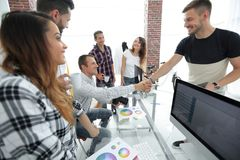 同事握手在一个创造性的办公室 免版税库存照片