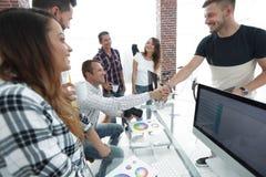 同事握手在一个创造性的办公室 图库摄影