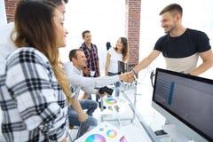 同事握手在一个创造性的办公室 库存图片