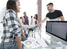 同事握手在一个创造性的办公室 免版税库存图片