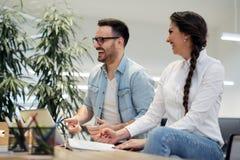 同事聊天,一起坐在办公室桌上 免版税库存图片