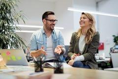 同事聊天,一起坐在办公室桌上 免版税库存照片