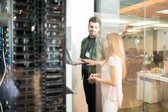 同事谈论在办公室服务器室 免版税库存图片