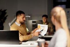 同事谈论项目在附近的办公室 免版税库存图片