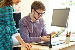 年轻同事-看对颜色油漆调色板的manand妇女 免版税库存图片