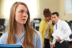 同事说闲话的女实业家在办公室 库存照片