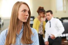 同事说闲话的女实业家在办公室 免版税库存照片