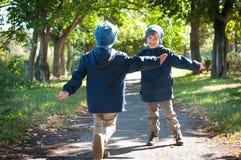 同卵双生互相拥抱的兄弟奔跑 库存照片