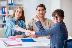 同意抵押合同的年轻家庭在新房的银行中 库存图片