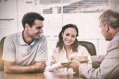 同房地产开发商的微笑的夫妇签署的合同 免版税库存图片