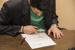 年轻同放大镜的人审查的合同 免版税图库摄影