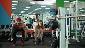 同时屈曲胳膊的男人和妇女由举的哑铃,在健身房的锻炼 股票录像