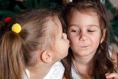 同样年龄谎言的两个逗人喜爱的姐妹在新年树旁边的 一 图库摄影