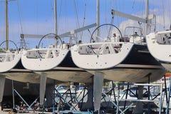 同样游艇在干燥停车处连续站立在小游艇船坞在一个晴朗的夏日 设备在水线下的帆船 免版税库存图片