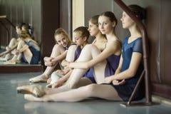 同样的五位年轻舞蹈家跳舞服装,休息坐的o 免版税库存照片
