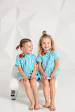 同样绿松石的两个小女朋友在有白色墙壁的一个演播室穿戴坐一把椅子 免版税库存图片